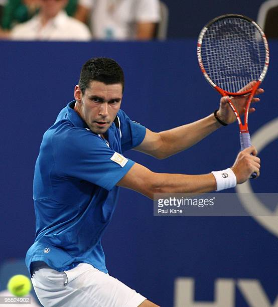 Victor Hanescu of Romania plays a backhand in his match against Lleyton Hewitt of Australia in the Group A match between Australia and Romania during...