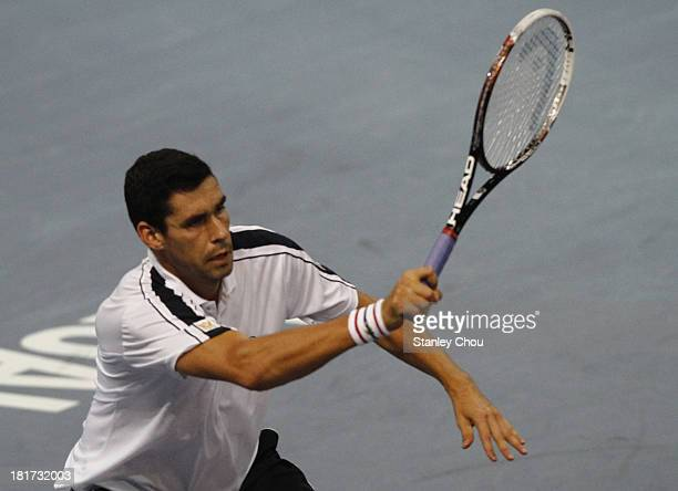 Victor Hanescu of Romania plays a forehand shot against Vasek Pospisil of Canada during day two of the 2013 Malaysian Open at Putra Stadium on...