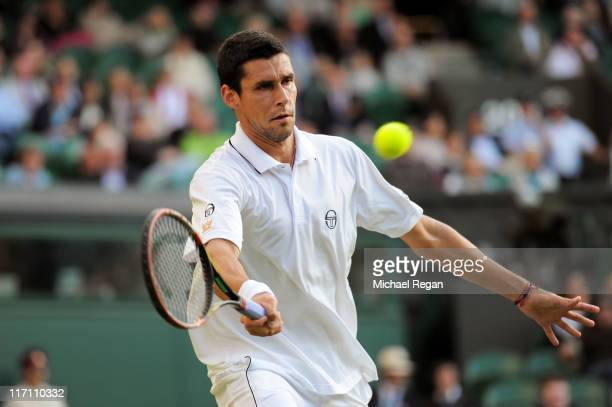 Victor Hanescu of Romania returns a shot during his second round match against Andy Roddick of the United States on Day Three of the Wimbledon Lawn...