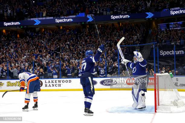 Victor Hedman and Andrei Vasilevskiy of the Tampa Bay Lightning celebrate the team's 1-0 win against the New York Islanders as Matt Martin reacts in...
