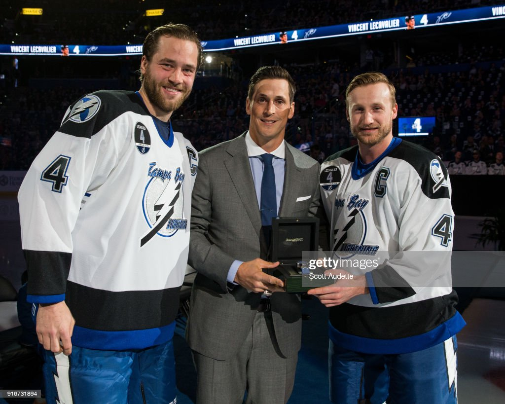 Victor Hedman #77 and Steven Stamkos #91 of the Tampa Bay Lightning give former teammate Vincent Lecavalier a gift during the the jersey retirement ceremony for Vincent Lecavalier at Amalie Arena on February 10, 2018 in Tampa, Florida.