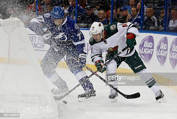 Victor Hedman of the Tampa Bay Lightning and Justin Fontaine of the Minnesota Wild battle of a loose puck at the Tampa Bay Times Forum on October 17...