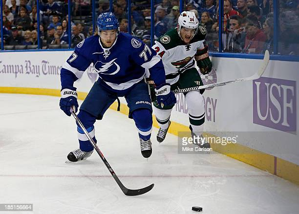 Victor Hedman of the Tampa Bay Lightning and Matt Cooke of the Minnesota Wild battle for a loose puck at the Tampa Bay Times Forum on October 17 2013...