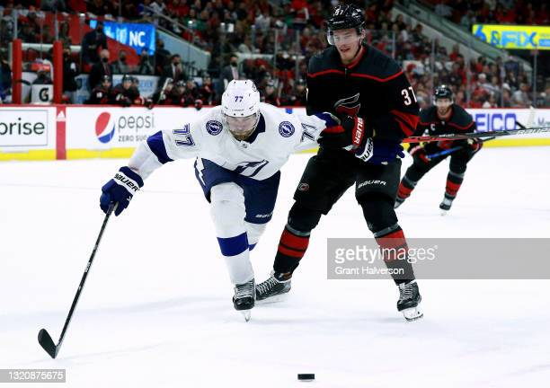 Victor Hedman of the Tampa Bay Lightning battles Andrei Svechnikov of the Carolina Hurricanes for the puck during the third period in Game One of the...