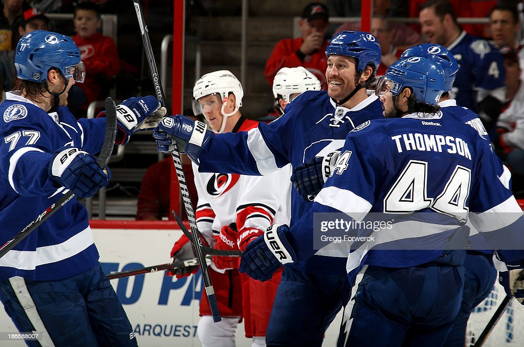 Victor Hedman #77 of the Tampa Bay Lightning celebrates his second-period goal against the Carolina Hurricanes with teammates Ryan Malone #12, B.J. Crombeen #19 and Nate Thompson #44 during their NHL game at PNC Arena on November 1, 2013 in Raleigh, North Carolina.