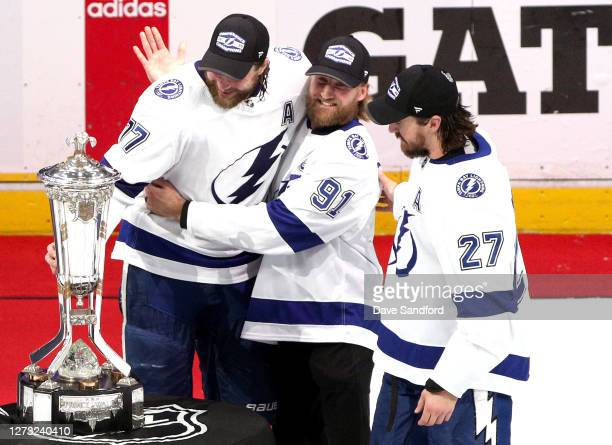 Victor Hedman, Steven Stamkos and Ryan McDonagh of the Tampa Bay Lightning pose with the Prince of Wales Trophy after their 2-1 win in the first...