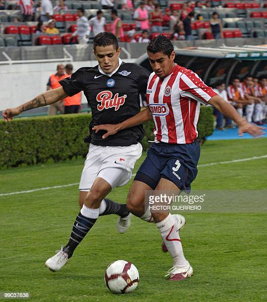 Victor Hugo Ayala of Libertad of Paraguay vies for the ball with Patricio Araujo of Guadalajara of Mexico during their Copa Libertadores 2010...