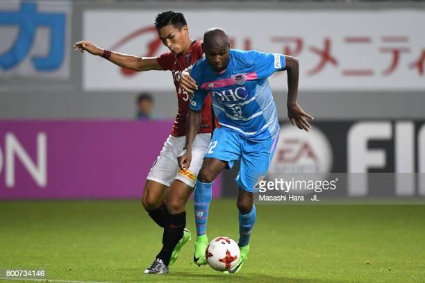 Victor Ibarbo of Sagan Tosu and Tomoaki Makino of Urawa Red Diamonds compete for the ball during the JLeague J1 match between Sagan Tosu and Urawa...