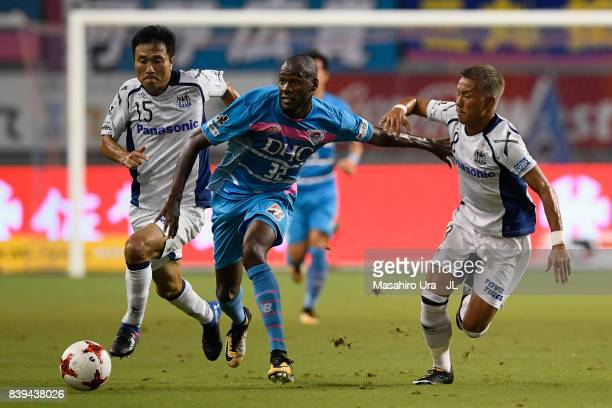 Victor Ibarbo of Sagan Tosu controls the ball under pressure of Yasuyuki Konno and Yosuke Ideguchi of Gamba Osaka during the JLeague J1 match between...