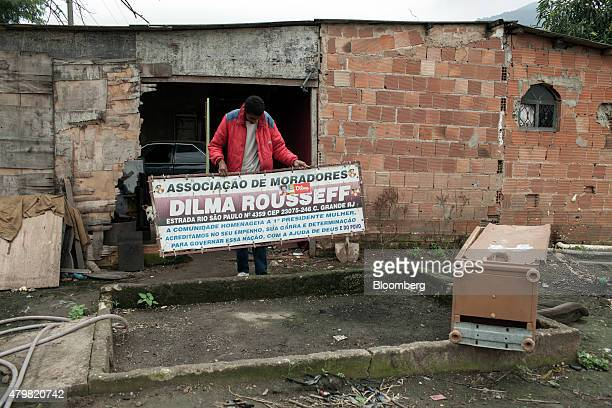 Victor Jonathan Coelho do Santos shows a reporter a discarded sign that the residents association had previously hung at the entrance to the Dilma...
