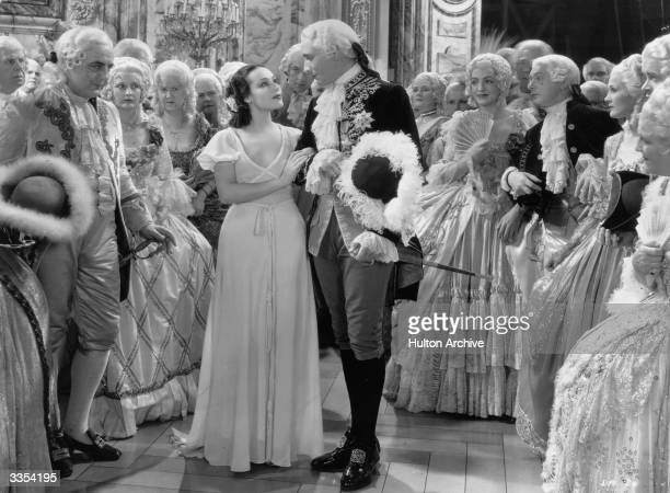 Victor Jory and Dolores del Rio surrounded by a bewigged and sumptuously dressed cast in a scene from 'Madame Du Barry' a Warner production