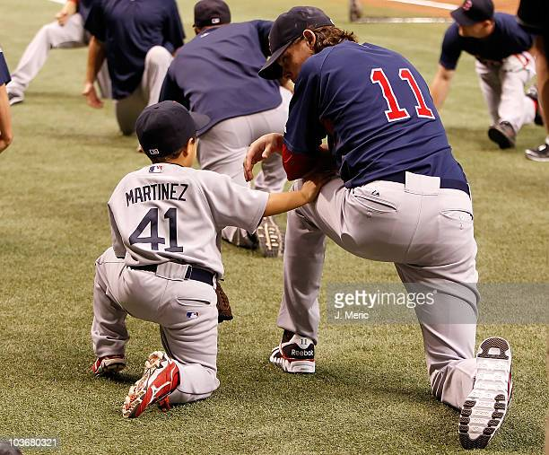 Victor Jose Martinez the son of catcher Victor Martinez talks with pitcher Clay Buchholz of the Boston Red Sox just prior to the start of the game...