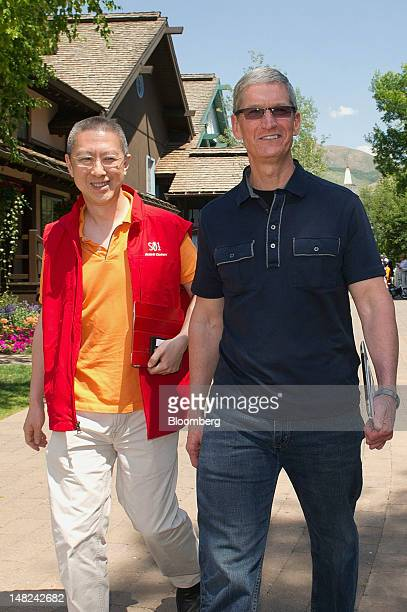 Victor Koo, chief executive officer of Youku Inc., left, walks with Tim Cook, chief executive officer of Apple Inc., during the Allen & Co. Media and...