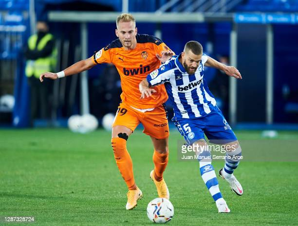Victor Laguardia of Deportivo Alaves duels for the ball with Uros Racic of Valencia CF during the LaLiga Santander match between Alaves and Valencia...