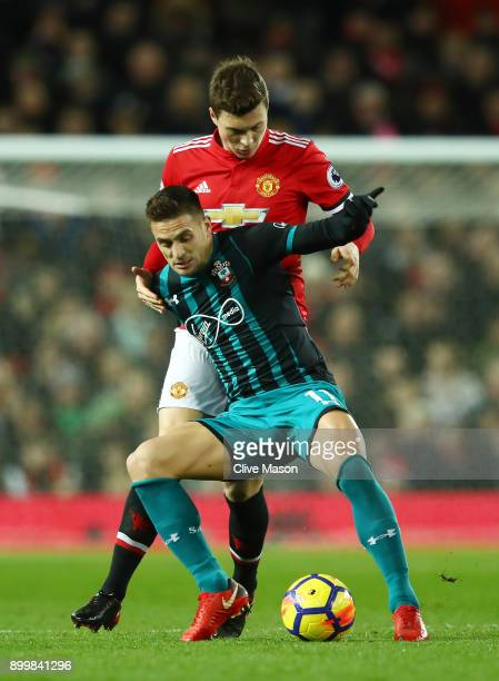 Victor Lindelof of Manchester United and Dusan Tadic of Southampton battle for possession during the Premier League match between Manchester United...