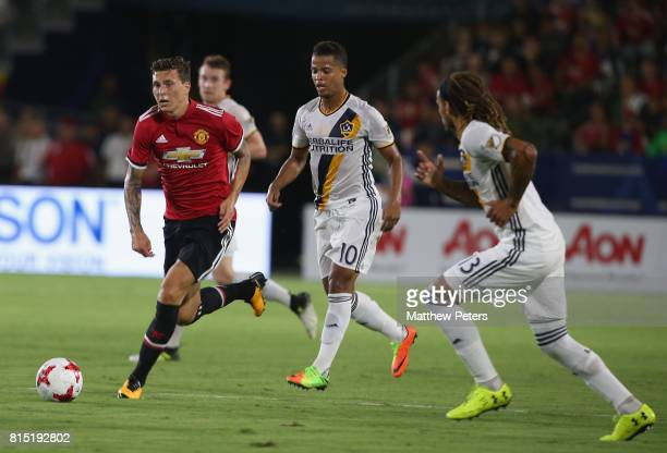 Victor Lindelof of Manchester United in action with Giovani dos Santos of LA Galaxy during the preseason friendly match between LA Galaxy and...