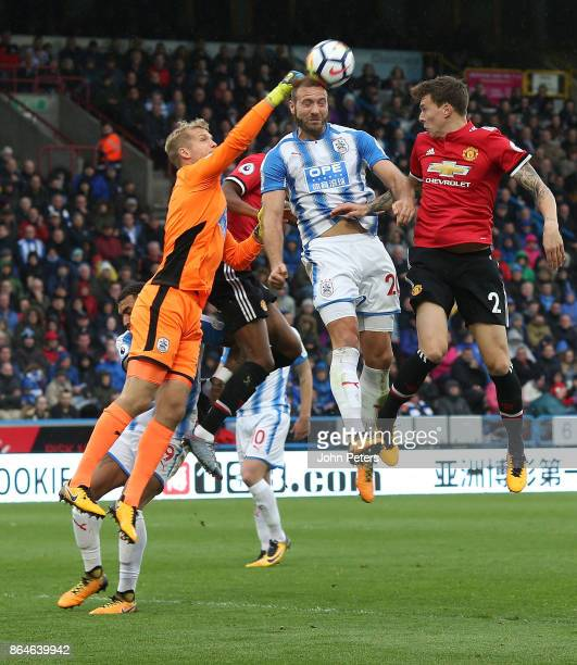 Victor Lindelof of Manchester United in action with Jonas Lossi and Laurent Depoitre of Huddersfield Town during the Premier League match between...