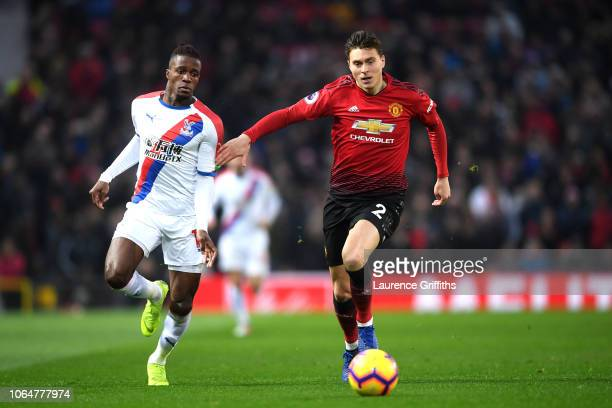Victor Lindelof of Manchester United runs with the ball past Wilfried Zaha of Crystal Palace during the Premier League match between Manchester...