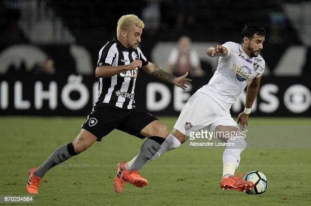 Victor Luis of Botafogo battles for the ball with Henrique Dourado of Fluminense during the match between Botafogo and Fluminense as part of...