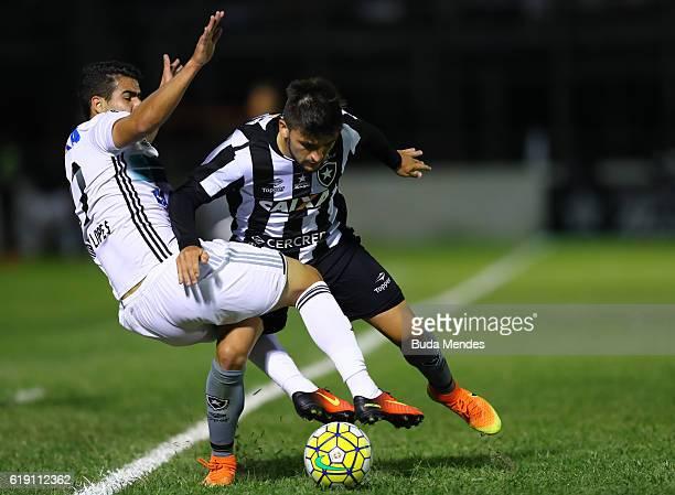 Victor Luis of Botafogo struggles for the ball with Thiago Lopes of Coritiba during a match between Botafogo and Coritiba as part of Brasileirao...