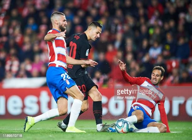 Victor Machin Perez 'Vitolo' of Club Atletico de Madrid competes for the ball with Victor Diaz of Granada CF during the Liga match between Granada CF...