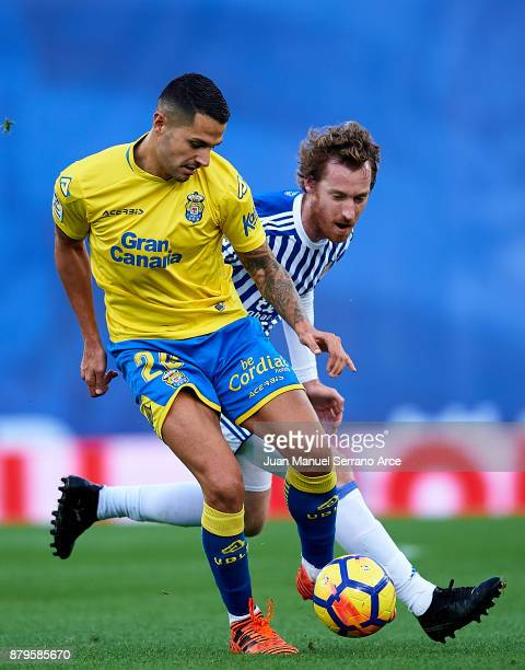 Victor Machin Perez 'Vitolo' of UD Las Palmas duels for the ball with David Zurutuza of Real Sociedad during the La Liga match between Real Sociedad...