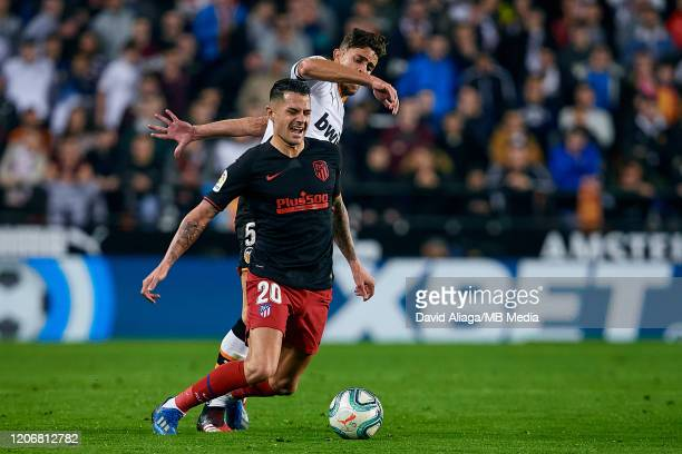 Victor Machin Vitolo of Atletico de Madrid competes for the ball with Gabriel Paulista of Valencia CF during the Liga match between Valencia CF and...