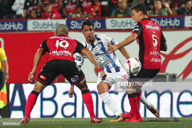 Victor Malcorra of Tijuana Roberto de la Rosa of Pachuca and Damian Muslo of Tijuana fight for the ball during the seventh round match between...