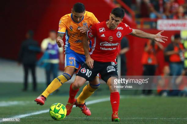 Victor Malcorra of Tijuana struggles for the ball with Ismael Sosa of Tigres during the semi final second leg match between Tijuana and Tigres UANL...