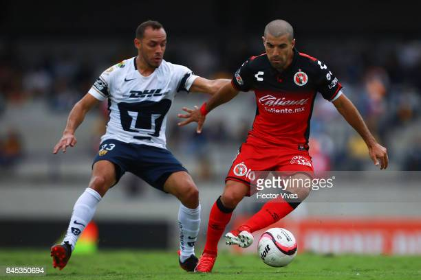 Victor Malcorra of Tijuana struggles for the ball with Marcelo Diaz of Pumas during the 8th round match between Pumas UNAM and Tijuana as part of the...