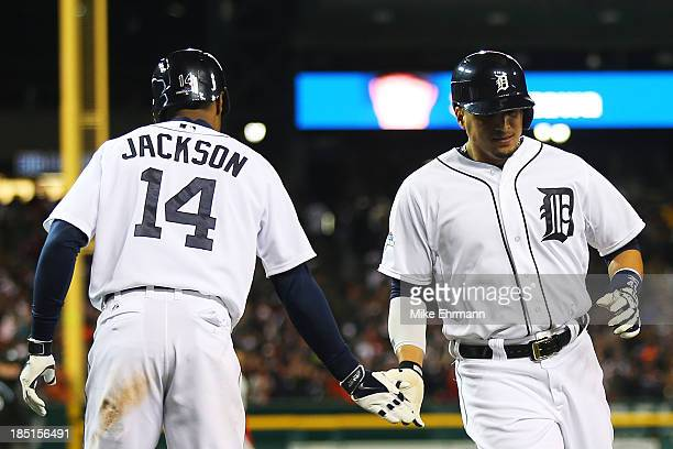Victor Martinez celebrates scoring on a single by Brayan Pena with Austin Jackson in the sixth inning against the Boston Red Sox during Game Five of...