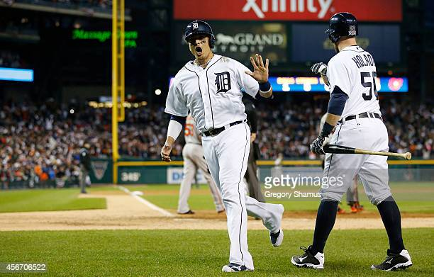 Victor Martinez is congratulated by Bryan Holaday of the Detroit Tigers after he scored on an RBI double by JD Martinez in the ninth inning during...
