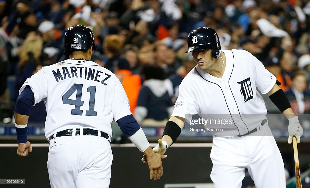 Victor Martinez #41 is congratulated by Bryan Holaday #50 of the Detroit Tigers after he scored on an RBI double by J.D. Martinez #28 in the ninth inning during Game Three of the American League Division Series at Comerica Park on October 5, 2014 in Detroit, Michigan.