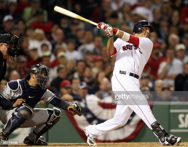 Victor Martinez of the Boston Red Sox gets a hit as Jorge Posada of the New York Yankees defends on April 4, 2010 during Opening Night at Fenway Park...