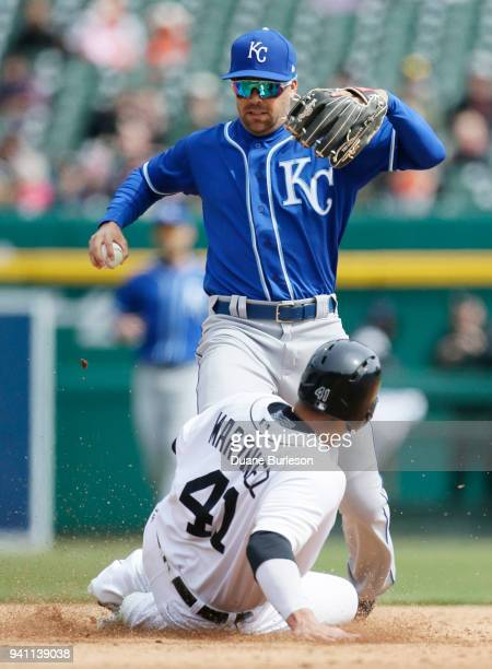 Victor Martinez of the Detroit Tigers beats second baseman Whit Merrifield of the Kansas City Royals to second base after Merrifield dropped the ball...