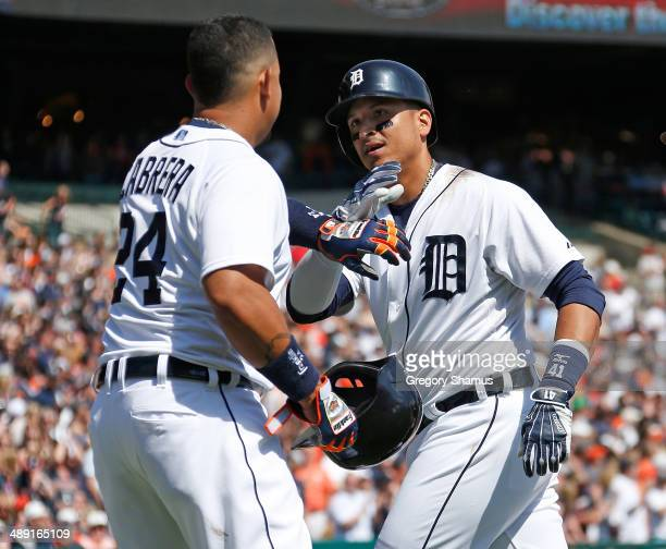 Victor Martinez of the Detroit Tigers celebrates his threerun home run with Miguel Cabrera during the seventh inning against the Minnesota Twins at...