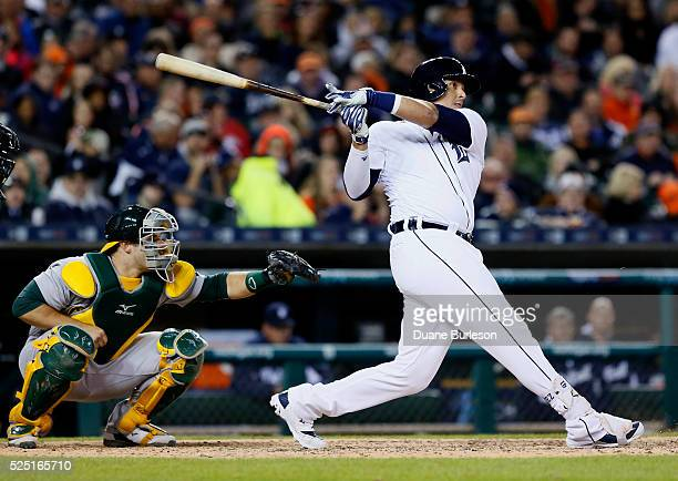 Victor Martinez of the Detroit Tigers hits a threerun home run with catcher Josh Phegley of the Oakland Athletics behind the plate during the sixth...