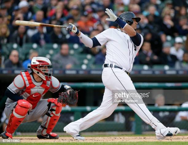 Victor Martinez of the Detroit Tigers hits an RBIdouble in front of catcher Roberto Perez of the Cleveland Indians during the first inning at...