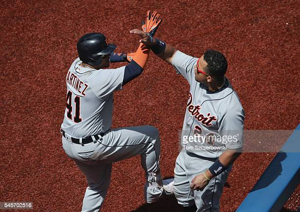 Victor Martinez of the Detroit Tigers is congratulated by Miguel Cabrera after hitting a solo home run in the eighth inning during MLB game action...