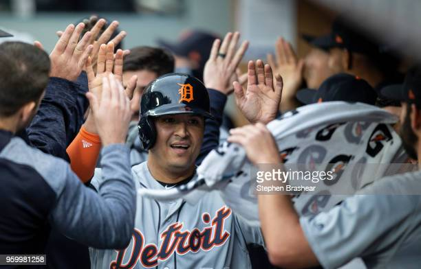 Victor Martinez of the Detroit Tigers is congratulated by teammates in the dugout after scoring a run on a double by John Hicks of the Detroit Tigers...