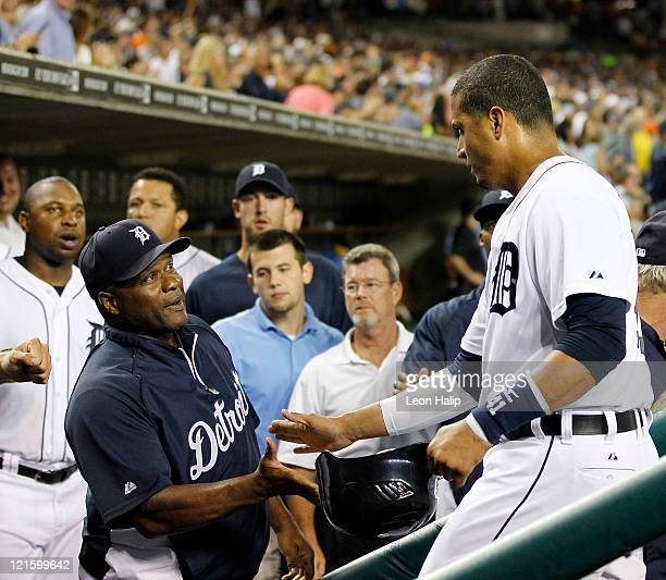 Victor Martinez of the Detroit Tigers scores in the fifth inning and is congratulated by Lloyd McClendon during the game against the Cleveland...