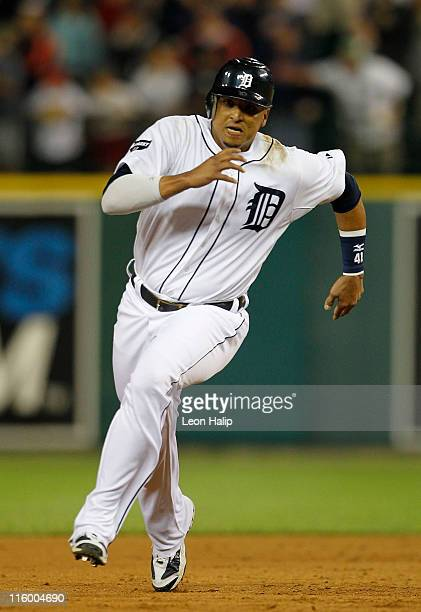 Victor Martinez of the Detroit Tigers scores the game winning run in the tenth inning on a triple from Ramon Santiago after his as the Tigers...
