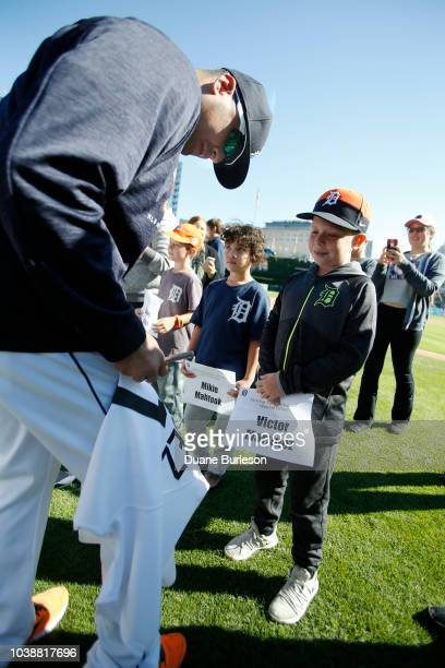 Victor Martinez of the Detroit Tigers signs his jersey for tenyearold Lucas Sides of Roseville Michigan during fan appreciation day at Comerica Park...