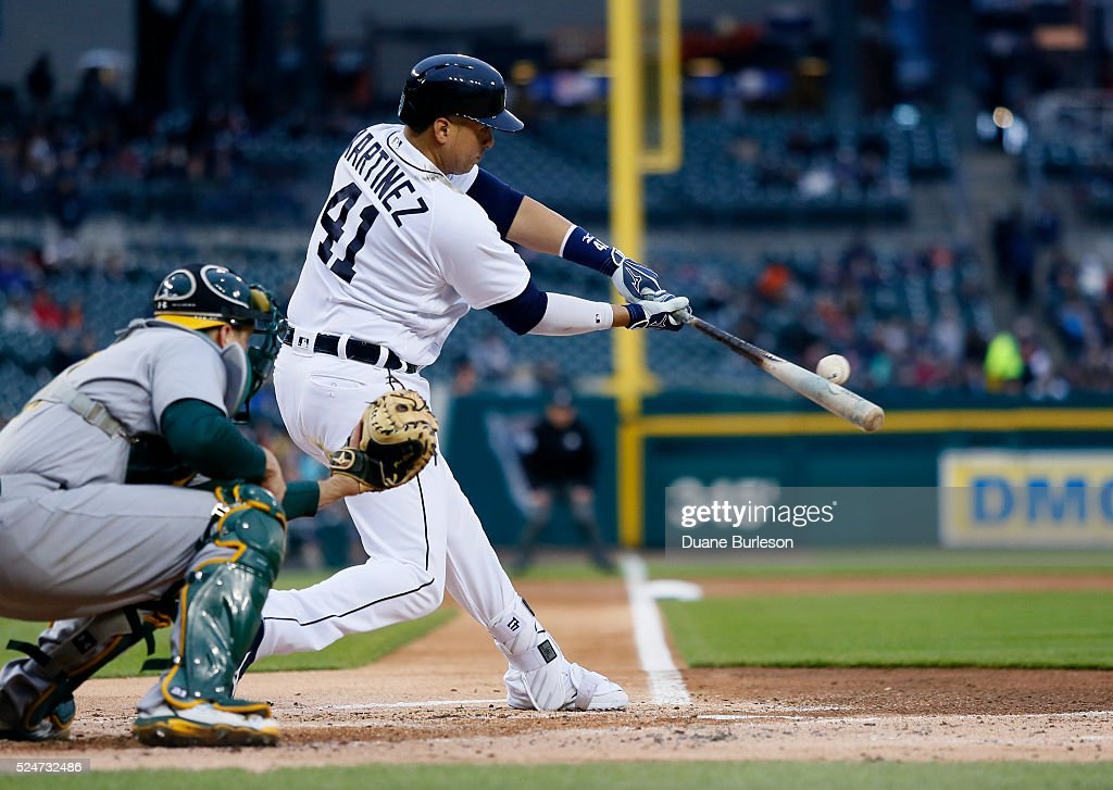 Victor Martinez #41 of the Detroit Tigers singles as catcher Stephen Vogt #21 of the Oakland Athletics works behind the plate during the first inning at Comerica Park on April 26, 2016 in Detroit, Michigan. The Athletics defeated the Tigers 5-1.