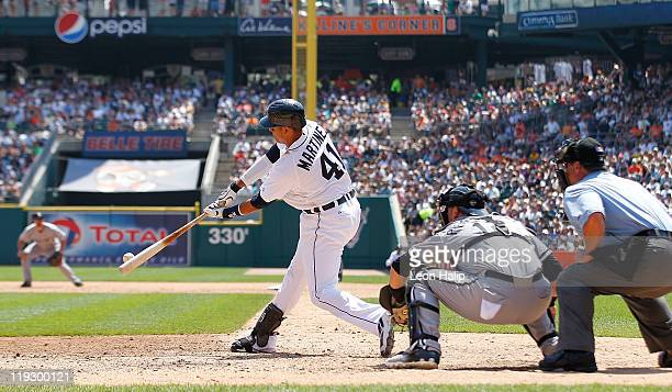 Victor Martinez of the Detroit Tigers singles to right field scoring Andy Dirks and Magglio Ordonez in the six inning during the game against the...