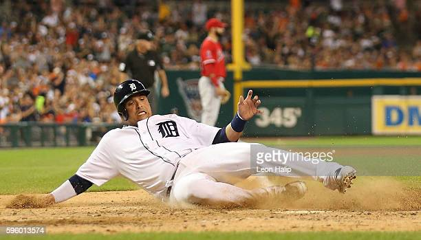 Victor Martinez of the Detroit Tigers slides home safe after scoring on the double by teammate JD Martinez during the sixth inning of the game...