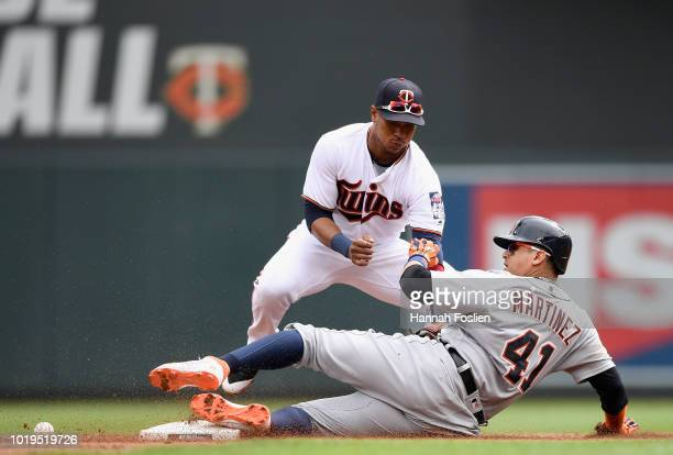 Victor Martinez of the Detroit Tigers slides in safely to second base with a double as the ball gets away from Jorge Polanco of the Minnesota Twins...