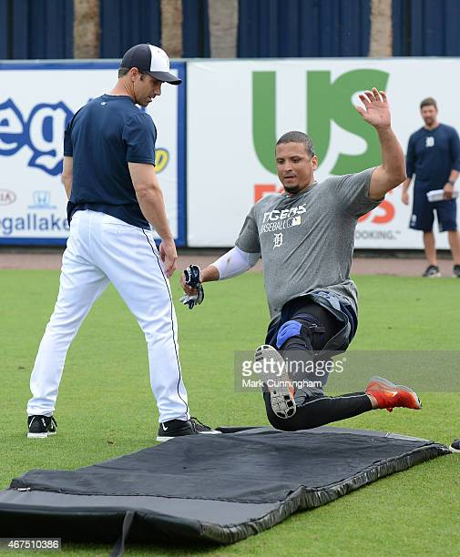 Victor Martinez of the Detroit Tigers works on a sliding drill while manager Brad Ausmus looks on prior to the Spring Training game against the Miami...