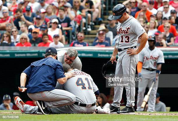 Victor Martinez the Detroit Tigers is helped to his feet by Manager Brad Ausmus and First Base Coach Omar Vizquel after being hit by a pitch in the...