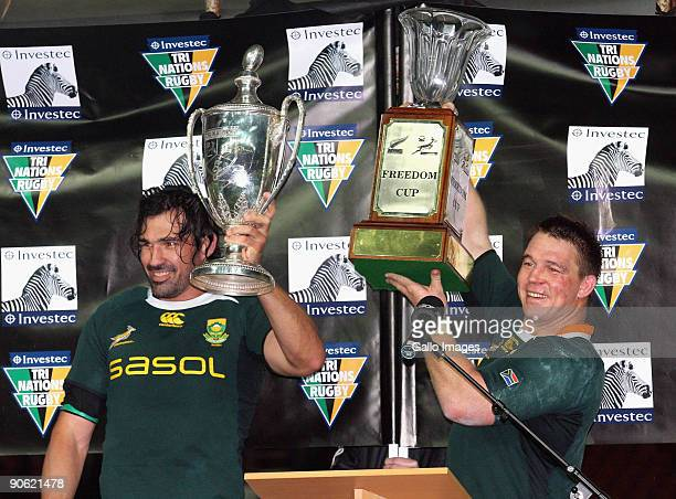 Victor Matfield of South Africa holds the Tri Nations trophy and team mate John Smit holds the Freedom Cup after winning the Tri Nations Test between...